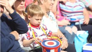 A young boy watches the Twelfth of July parade with his family, Richill, Armagh, 12 July 2017