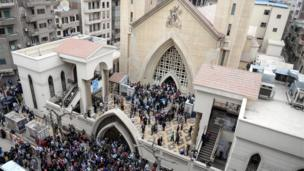 People gather in front of Mar Girgis church after a bomb explosion