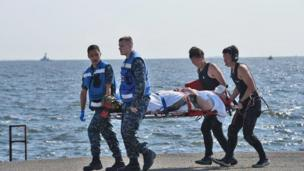 an injured USS Fitzgerald personnel being carried by US military personnel (L) and Japanese Maritime Self-Defense Force members (R)