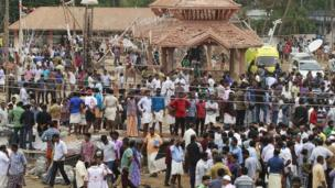 People gather inside the compound of a temple after a fire broke out at a temple in Kollam in the southern state of Kerala