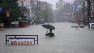 An Indian man holding an umbrella struggles along a flooded street in Agartala, Tripura.