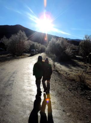 Hermanos caminando juntos hacia una montaña