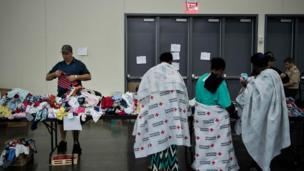 Flood victms wey wear Red Cross blanket dey look for wia to stay for one place for George R. Brown Convention Centre