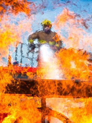 Пожарный из отдела тушения пожаров и проведения спасательных операции ВВС Великобритании тушит огонь