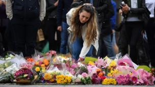 A woman lays flowers at a pedestrian crossing on the south side of London Bridge, close to Borough Market in London.