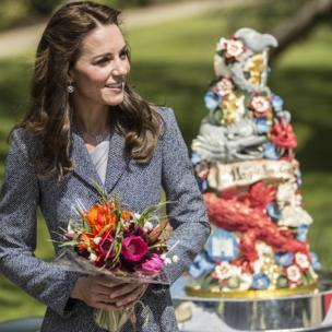 The Duchess of Cambridge walks past an ornate cake decorated with dragons and magical creatures.