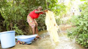 A woman washes at a stream