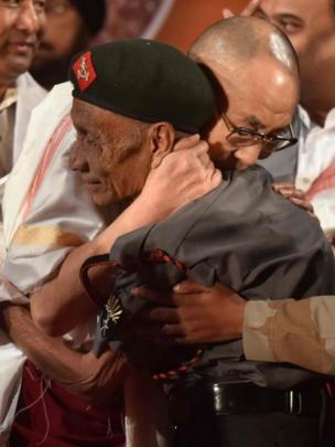 In this photograph taken on 2 April 2017, Tibetan spiritual leader the Dalai Lama (L) shakes hands with retired Assam Rifles personnel Naren Chandra Das
