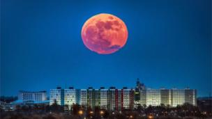 Moon, pictured large and reddish in tone, above Hull apartments in Yorkshire, UK