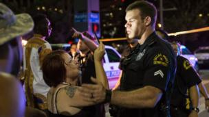 Woman takes photograph of police officer on street in Dallas, Texas - July 2016