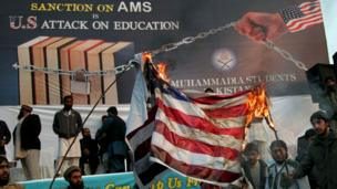 Supporters of Pakistani religious parties burn a representation of a U.S. flag during a rally in Lahore, Pakistan, Sunday, Jan. 8, 2017. Hundreds of Pakistani religious parties rallied in Lahore to,)
