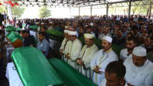 Imams lead the prayers as mourners gather for the funeral of victims of the attack on a wedding party