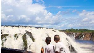 Dos hermanos conversando en frente de una cascada.