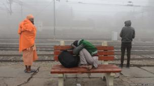 Indian passengers wait for a train amidst dense smog at a railway station in Amritsar on November 7, 2017