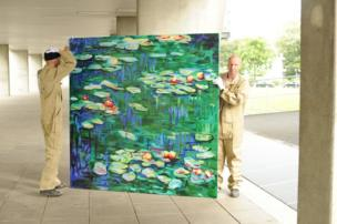Two men moving a canvas