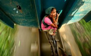 طفلة تجلس على الفاصل بين عربتي قطار