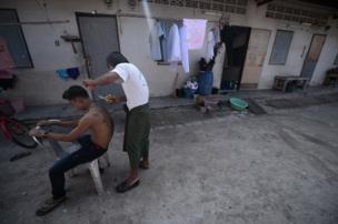 ขณะที่ชายชาวเมียนมาหลายคนที่ยังนุ่งโสร่ง อย่างในภาพนี้ ชายคนนี้กำลังตัดผมให้กับเพื่อนบ้านของเขา