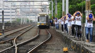 Light Rail Transit (LRT) mock passengers use their hands to cover their heads as they pass through a walkway beside the train tracks during a metrowide simultaneous earthquake drill in metro Manila