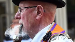 Orange man smoking a pipe while parading through the streets of Belfast, 12 July 2017