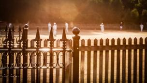 A cricket match seen from behind a fence