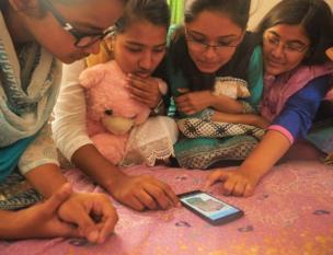 أطفال يتفقدون هاتف محمول