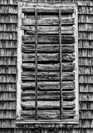 A black and white image of wood nailed across a window