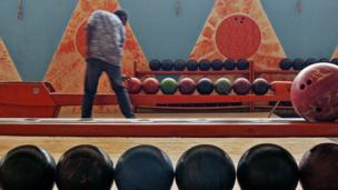 man taking bowling ball from queue in an art deco bowling alley