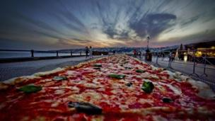 The pizza laid out along the seafront in the Italian city if Naples.