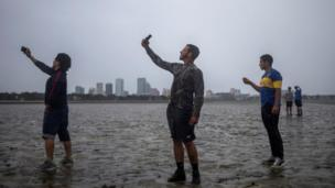 People in Tampa take photographs in drained bay with skyline in background