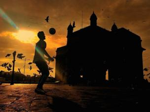 A boy plays football at dusk in the shadow of the Gateway of India in Mumbai