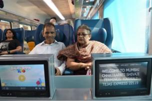 In this photograph taken on May 22, 2017, Indian passengers watch television screens onboard the Tejas Express luxury train during its first journey between Mumbai and Goa in Mumbai.