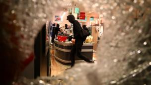 A protester is seen through smashed glass looting what appears to be a supermarket in Hamburg