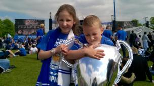 Two fans holding a balloon trophy