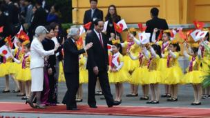 Japan's Emperor Akihito (2nd R) waves to children waving flags as he walks next to Vietnamese President Tran Dai Quang (1st R), Japan's Empress Michiko (L) and Quang's spouse Nguyen Thi Hien during an official welcoming ceremony at the presidential palace in Hanoi on March 1, 2017. Japan's emperor and empress departed February 28 for their first trip to Vietnam to meet families of former Japanese soldiers to help heal wounds left over from its occupation of the country during World War II.
