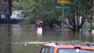 A man stands in chest-deep water on a flooded street in Houston.
