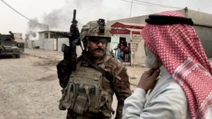 جندي بالقوات الخاصة العراقية يتحدث مع مدني من الموصل