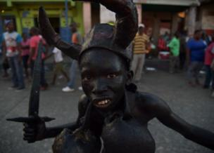 A youth painted with a mixture of cane sugar syrup and coal and wearing skulls in Port-au-Prince, Haiti. Photo: 28 February 2017