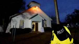 A police hat hangs outside the white exterior of the church