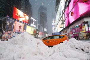 سيارة تعبر أكواما من الثلوج في ميدان تايمز سكوير بنيويورك