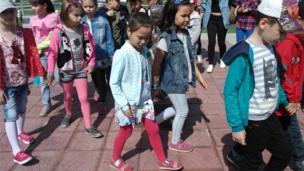 เด็กหลายคนเดินจูงมือเรียงเป็นแถว ซึ่งที่ประเทศนี้สามารถพบเห็นคนหลายหลายเชื้อชาติ ตั้งแต่คาซัค ยูเครน รัสเซีย เยอรมัน เพราะเป็นปนะเทศที่อยู่ระหว่างรอยต่อของทวีปเอเชีย-ยุโรป