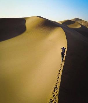 Two people make their way up a sand dune
