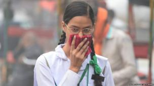 schoolgirl covers her face with a handkerchief amid heavy smog in the old quarters of New Delhi on November 8, 2017