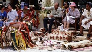 Queen Elizabeth II and Prince Philip, Duke of Edinburgh receiving gifts, while watching and photographing traditional dancers in Funafuti in Tuvalu on 27 October 1982 during the Royal Tour of the South Pacific.