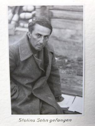 Yakov Jugashvili looks directly at the camera with one eyebrow raised, wearing a long dark military coat.