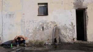 Bir mülteci binanın dışında saçını yıkıyor.