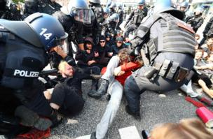 German police remove protesters who are blocking a street at a demonstration during the G20 summit in Hamburg, 7 July