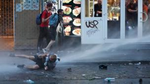 A man lies on the ground as riot police use water cannon against protesters on July 7