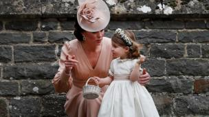 Duchess of Cambridge stands with her daughter Princess Charlotte, a bridesmaid