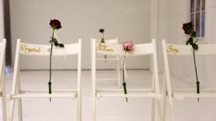 Three white chairs with the names of those killed
