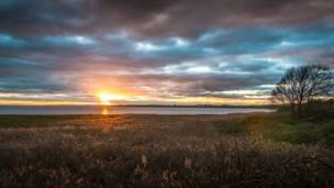 A moody sunset over the Usk Estuary at Newport Wetlands
